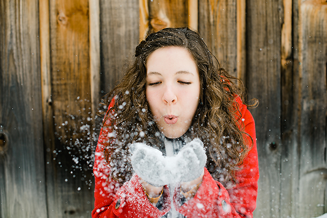 girl blowing snow in her senior portraits