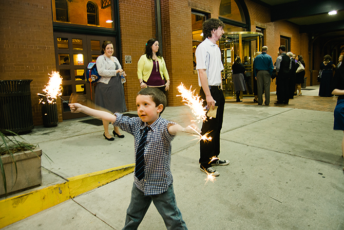kid playing with sparklers at a wedding reception