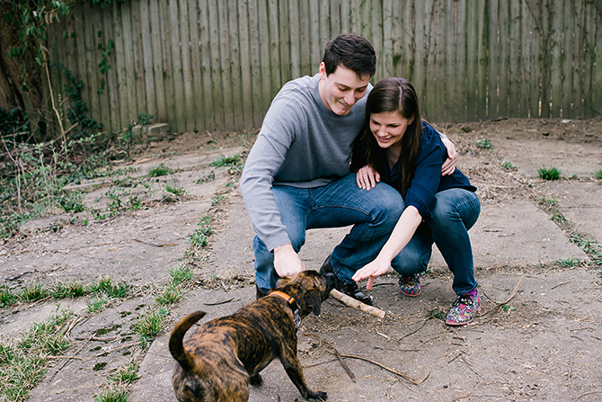 engagement photo of couple playing with their dog at home