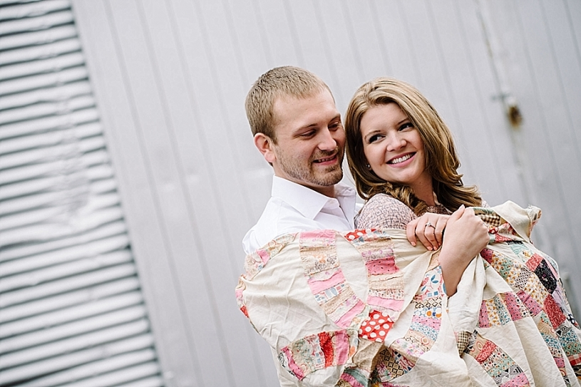 engagement pictures outside with vintage quilt